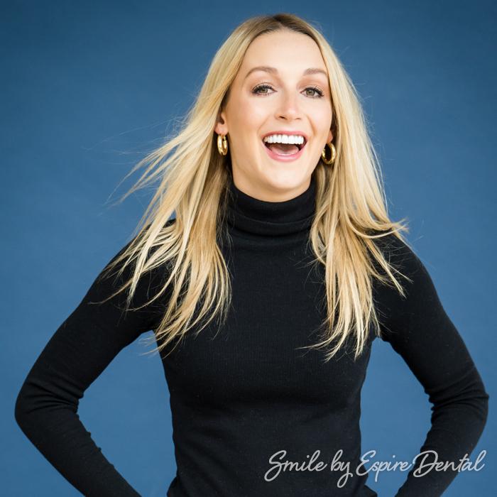 blonde woman in black turtleneck smiling